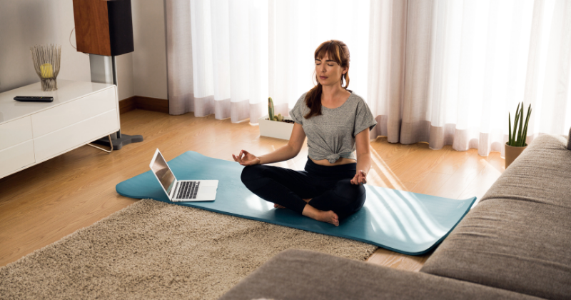 Woman doing yoga home workout, meditation, relaxation. Wellness Challenges to Improve Your Health - Whole Family Living