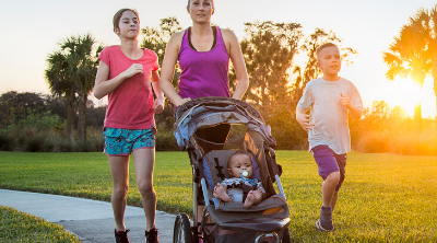Mom with kids jogging with stroller outside at sunset. Creating a fitness plan for the whole family - Whole Family Living
