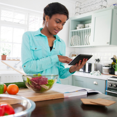 Woman looking a recipe on her digital device while cooking. 10 Healthy Cookbooks for Easy Family Meals - Whole Family LIving