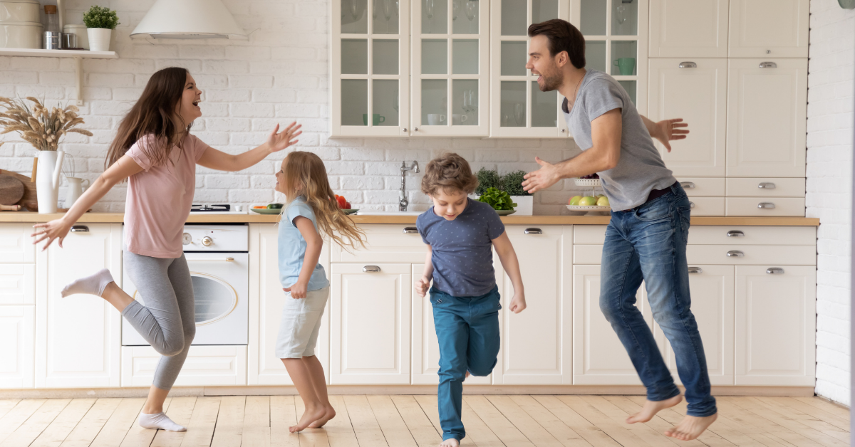 Family having an impromptu dance party in the kitchen. How to plan a family wellness challenge to stay active and healthy.