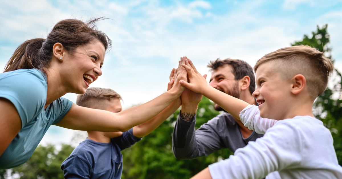 Family at the park, high-fiving while playing sports together. How to Plan a Family Wellness Challenge - Whole Family Living.