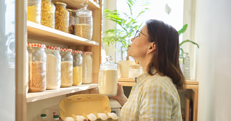 Woman looking for items in pantry with glass storage containers. How to Stock a Healthy Pantry - Whole Family Living