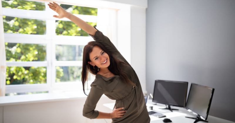 Young woman doing stretching exercises working in home office. Stay Active While Working From Home - Whole Family Living